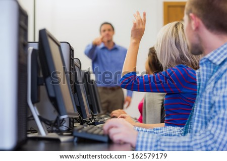 Teacher explaining to young college students in the computer room - stock photo