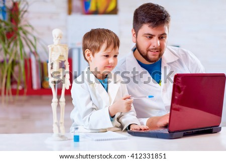 teacher explains a human body structure to little pupil with the help of laptop - stock photo