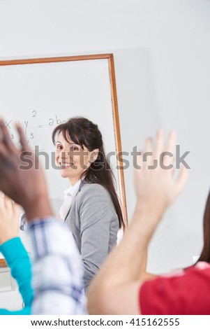 Teacher giving a class and students raising their hands