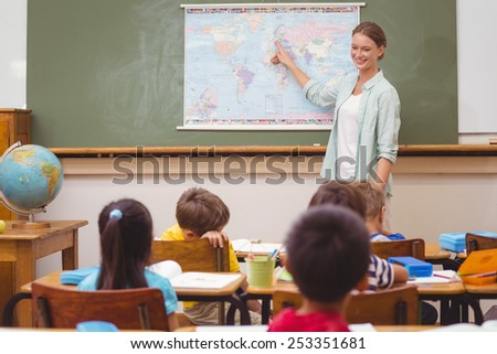 Teacher giving a geography lesson in classroom at the elementary school - stock photo