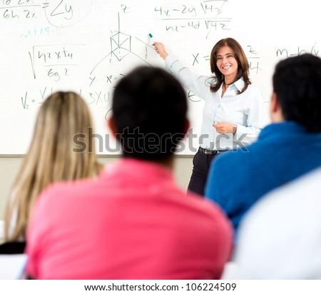 Teacher giving a lecture in a classroom and writing math formulas on the board - stock photo