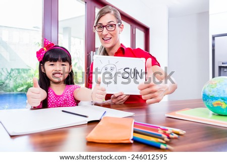 Teacher giving English language lessons to Chinese child - stock photo