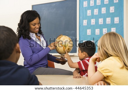 Teacher giving geography lesson in school classroom with globe. - stock photo