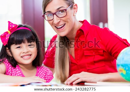 Teacher giving language lessons and doing homework to Chinese child - stock photo