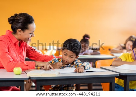 Teacher giving lesson to her students at school