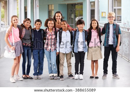 Teacher hanging out with group of elementary kids at school - stock photo