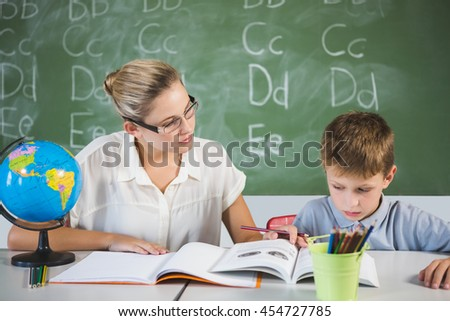 Teacher helping a boy with his homework in classroom at school - stock photo