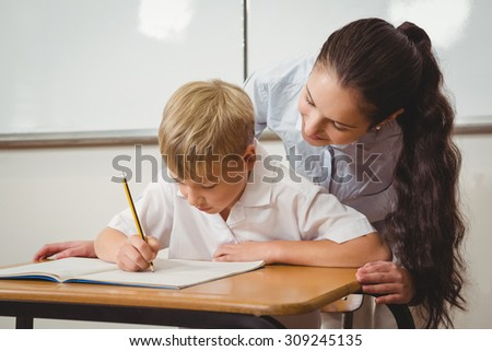 Teacher helping a student in class at the elementary school