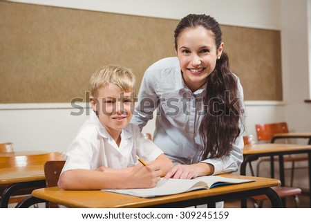 Teacher helping a student in class at the elementary school - stock photo