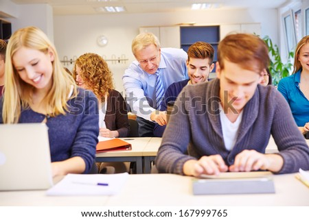 Teacher helping a student with laptop computer in a class in school - stock photo
