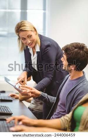 Teacher helping boy with tablet pc in the computer room - stock photo