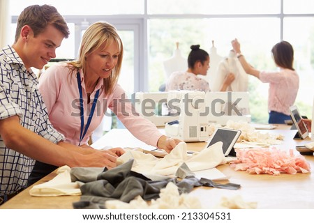 Teacher Helping College Students Studying Fashion And Design - stock photo