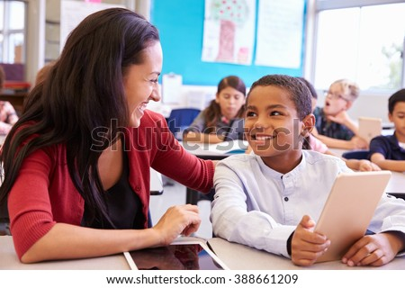 Teacher helping elementary school boy using tablet computer - stock photo
