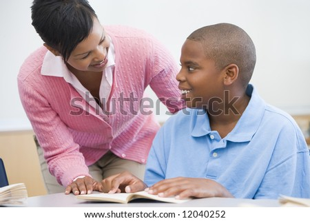 Teacher helping elementary school pupil with reading