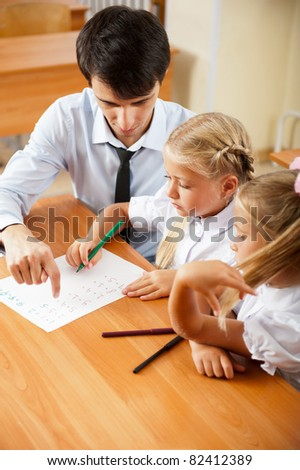 Teacher helping elementary school pupils with their tasks - stock photo