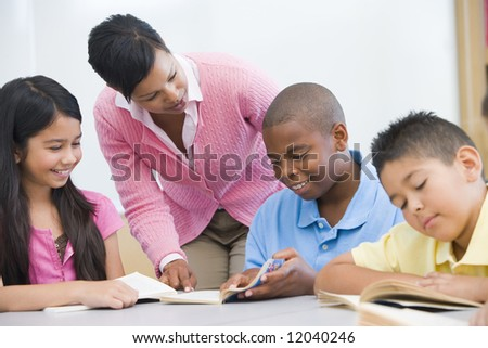 Teacher helping elementary school reading group - stock photo