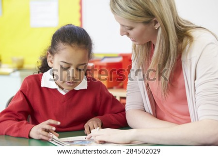 Teacher Helping Female Pupil With Practising Reading At Desk - stock photo