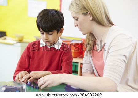Teacher Helping Male Pupil With Maths At Desk - stock photo