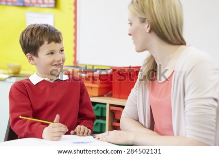 Teacher Helping Male Pupil With Practising Writing At Desk - stock photo