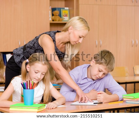 teacher helping pupil explains how to solve the task - stock photo