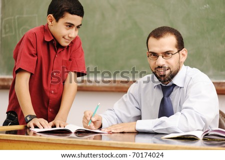 Teacher helping pupil in classroom to resolve schoolwork - stock photo