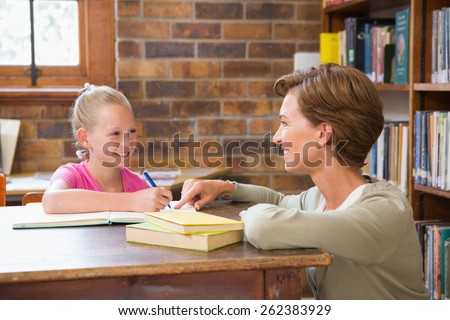 Teacher helping pupil in library at elementary school - stock photo