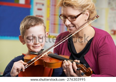 Teacher Helping Pupil To Play Violin In Music Lesson - stock photo