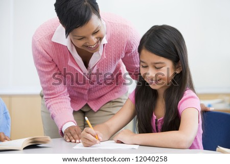Teacher helping pupil with written project