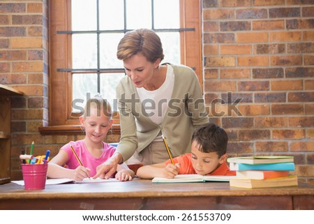 Teacher helping pupils in library at elementary school - stock photo