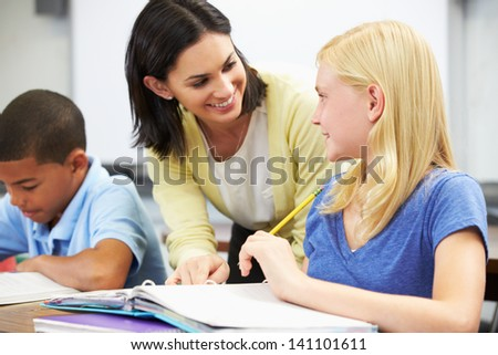 Teacher Helping Pupils Studying At Desks In Classroom - stock photo