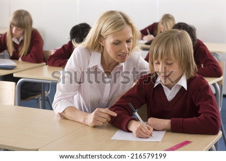 Teacher helping school boy with test in classroom - stock photo