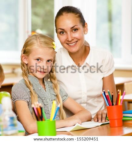 Teacher helping schoolgirl with schoolwork in classroom - stock photo