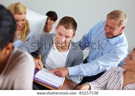 Teacher helping some students in university class - stock photo