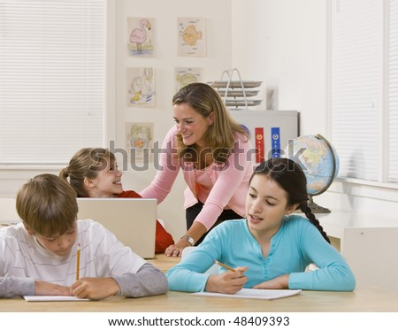 Teacher helping student - stock photo