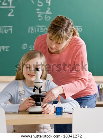 Teacher helping student adjust microscope in school science classroom - stock photo