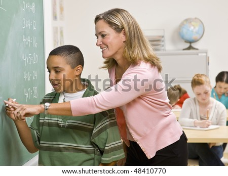 Teacher helping student at blackboard - stock photo