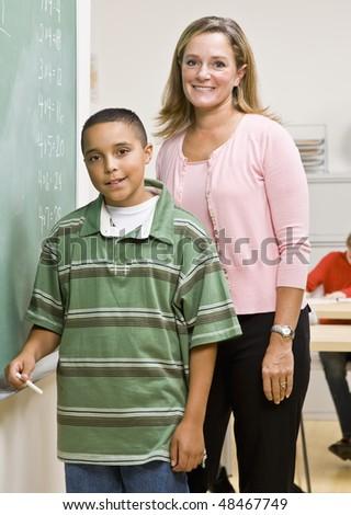 Teacher helping student at blackboard - stock photo