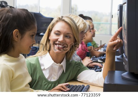Teacher helping student at computer terminal with students in background (depth of field/high key) - stock photo