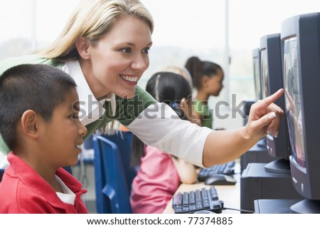 Teacher helping student at computer terminal with students in background (selective focus/high key) - stock photo