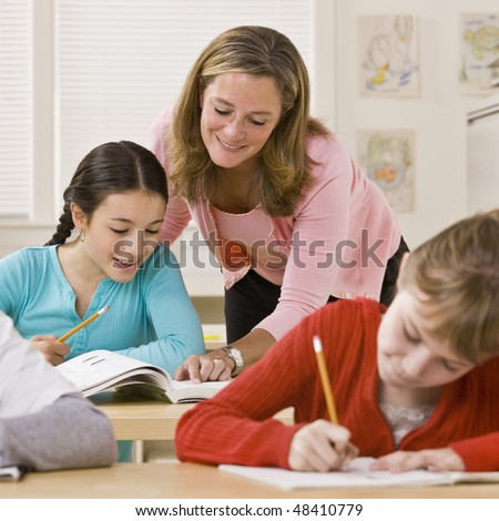 Teacher helping student in classroom - stock photo