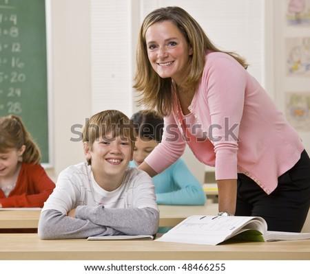 Teacher helping student in classroom - stock photo
