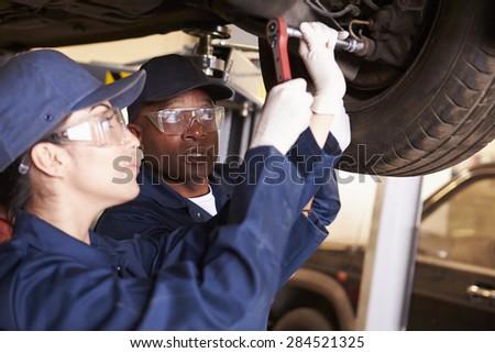 Teacher Helping Student Training To Be Car Mechanics - stock photo