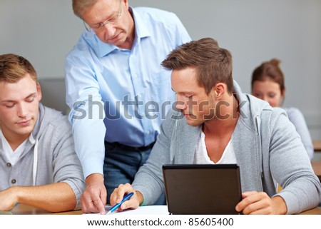 Teacher helping students learning in university class - stock photo