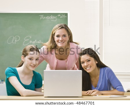 Teacher helping students on laptop - stock photo