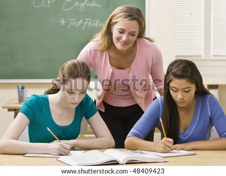 Teacher helping students study - stock photo