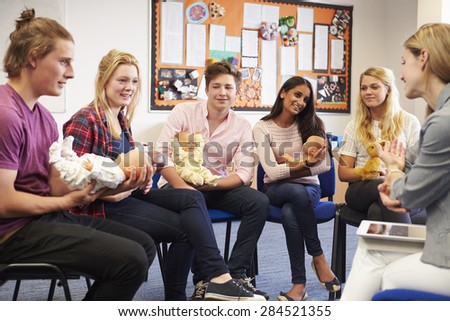 Teacher Helping Students Taking Childcare Course - stock photo