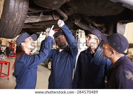 Teacher Helping Students Training To Be Car Mechanics - stock photo
