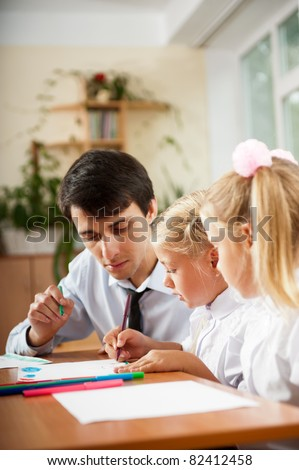 Teacher helping students with schoolwork in school classroom. Vertically framed shot.