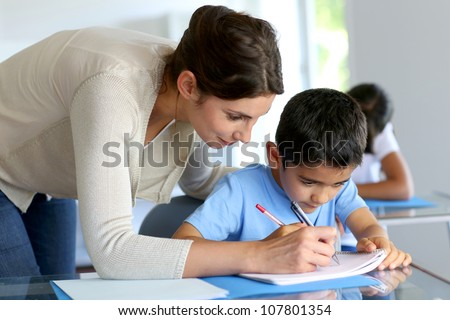 Teacher helping young boy with writing lesson