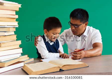 Teacher helps the student / learning in the classroom / photo of teen school Chinese boy / school teacher and student school theme - stock photo